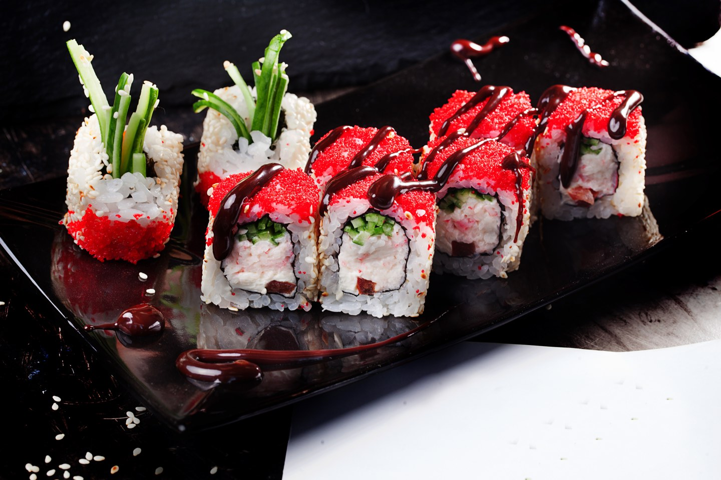 beautiful roll with crab, cucumber and tobiko caviar restaurant on black graphite board, sesame