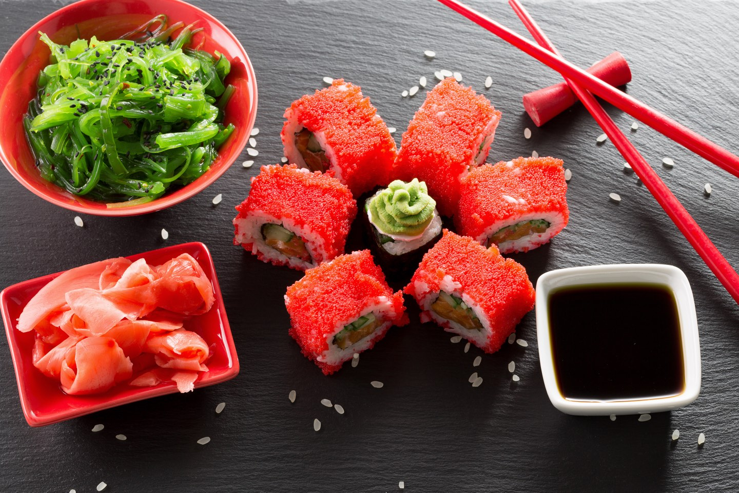 sushi and rolls with green sea salad on a slate table